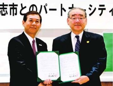 パートナーシティの協定書に調印した岩浅市長(右)と荒木市長=熊本県合志市の市役所(合志市提供)