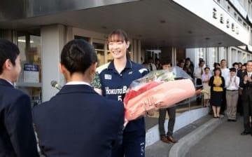 市役所に駆けつけた中央中の生徒から花束を受け取る松本選手