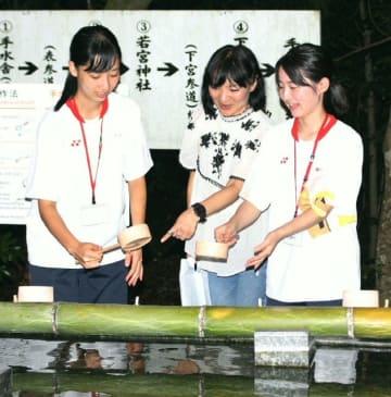 西田美紀さん(中央)の指導で、案内する箇所や分かりやすい伝え方を確認する宇佐高生=宇佐市の宇佐神宮