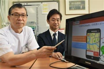 特許を取得した避難支援システムのイメージを説明する熊本赤十字病院の宮田昭副院長(左)と曽篠恭裕課長=1日、熊本市東区