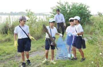 前川沿いの草むらに捨てられていた傘を拾う宮地小の4年生=八代市