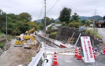 豪雨で崩落した新見市新見の市道。復旧工事が進んでいる=2日