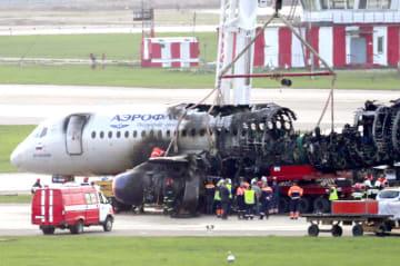 モスクワ郊外のシェレメチェボ空港で、炎上した事故機を調べる当局者ら=5月6日(タス=共同)