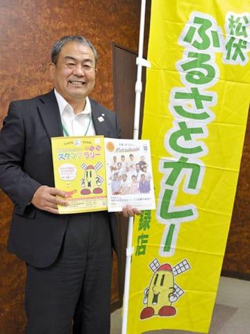 「松伏ふるさとカレースタンプラリー」をPRする鈴木勝町長。登録店は黄色いのぼり旗が目印=松伏町役場