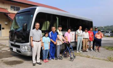 送迎バスの前で笑顔を見せる宅島施設長(左)ら=雲仙市、よろこびの里