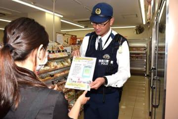 コンビニの店員に特殊詐欺の被害防止を呼び掛ける防犯アドバイザーの警察官 =横浜市青葉区