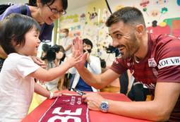 子どもたちとタッチを交わすJ1神戸のダビド・ビジャ選手(右)=神戸市中央区楠町7(代表撮影)