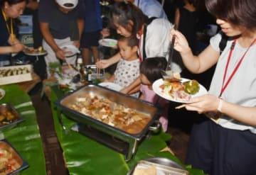 大隅産の食材をふんだんに使った料理を取り分ける参加者=大崎町のくにの松原キャンプ場