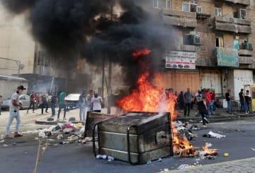 イラクの首都バグダッドで、火を放ち道路を封鎖するデモ参加者=2日(AP=共同)