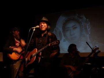 映画「佐藤敬子先生を探して」の映像を背景に歌うあがた森魚(9月29日、マンハッタンで)