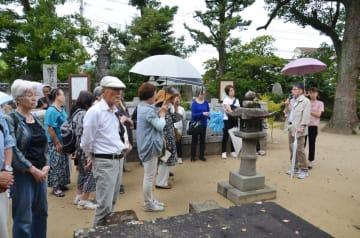 田島さん(右から2人目)の話に聞き入るバスハイク参加者=唐津市西寺町の近松寺