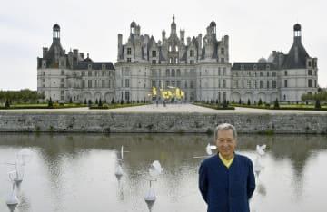 シャンボール城の前に立つ新宮晋さん。庭と水路に動く作品が配置されている=3日、フランス・シャンボール(共同)