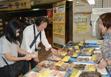 七厘村近くの鮮魚店で炭火焼き用の魚介を選ぶ買い物客。店舗には持ち込む食材は消費税10%という掲示がある