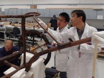 木製のチャリオットの構造を調べる日本とエジプトの合同プロジェクトのメンバー。右が栗本教授=2月中旬、大エジプト博物館保存修復センター(栗本教授提供)