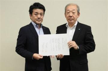 緊急時援助協定の協定書を持つ佐賀新聞社の森本貴彦メディア局長(左)と熊日の岩元俊弘専務=3日、熊本市中央区