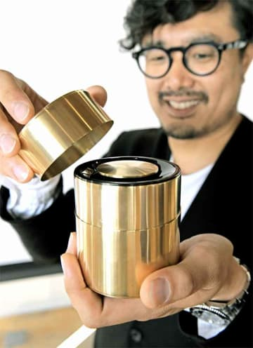パナソニックと商品化した茶筒のスピーカーを手にする開化堂の八木社長(京都市中京区のパナソニック・デザイン・キョウト)