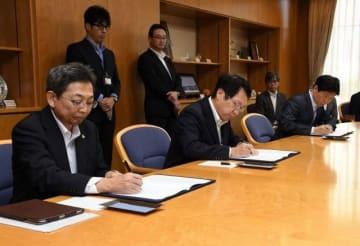 協定書に署名する(左から)深沢社長、加藤CEO、伊原木知事
