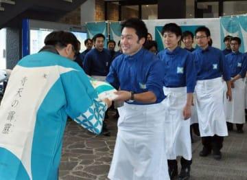 県内外での宣伝活動に向け三村知事(左)から霹靂の米袋を託されるPR隊員ら