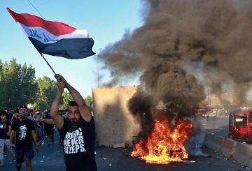 4日、イラクの首都バグダッドで、放火し道路をふさぐデモ隊(AP=共同)