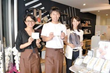 蕨もちを手に、左から町亜聖さん、関口慶太さん、工藤由貴子さん=1日、蕨市