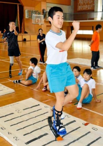 池田さん(左奥)から教わりながら、スポーツ用の義足に挑戦する福音小の児童