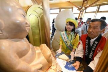 ビリケンさんに星空舞を奉納する佐伯さん(左)と栗原組合長=4日、大阪市浪速区の通天閣