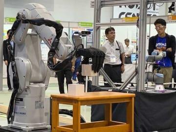 正確に部品をつかんむアーム型ロボットの実演に見入る来場者(京都府木津川市・精華町、けいはんなオープンイノベーションセンター)