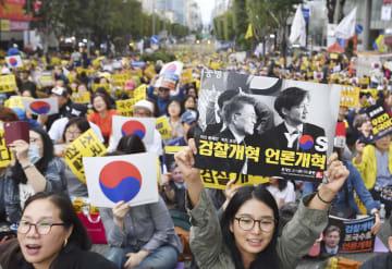 5日、ソウルで開かれた検察捜査を批判する集会。参加者は検察改革を訴えるパネルを掲げた(共同)