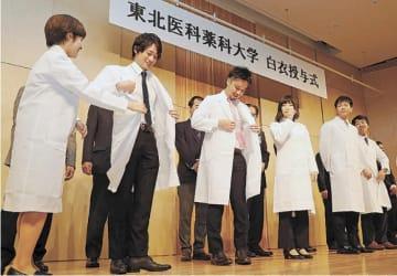 笑顔で白衣に袖を通す医学部生