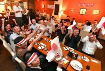 日本のトライに盛り上がるラグビーファンら=鹿児島市千日町のごはんのじかん