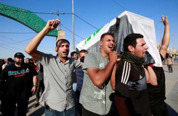 イラク中部ナジャフで、政府への抗議活動の際に死亡したデモ参加者のひつぎを担ぐ人たち=5日(ロイター=共同)