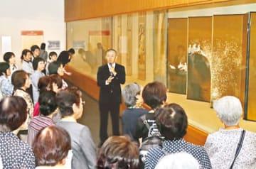 高島教授(中央)の話を聞きながら作品を鑑賞する来場者