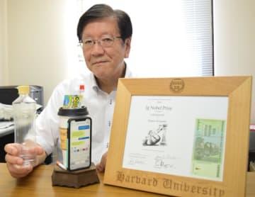 イグ・ノーベル賞で受賞したトロフィーなどを前に、研究で突き止めた5歳児の唾液量と同じ500ミリリットルのペットボトルを手に取る渡部教授=浦安市の明海大