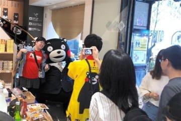 25周年を迎えた銀座熊本館。スーツを着たくまモンが一日店長を務め、駆けつけたファンと記念撮影し交流した=4日、東京・銀座