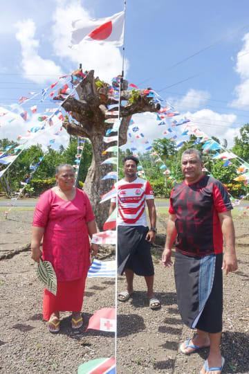 ラグビー日本代表ラファエレ・ティモシー選手の父ファアロゴさん(右)と母のマリアナさん(左)。自宅の敷地に日本国旗を掲げた=6日、サモア首都アピア郊外(共同)