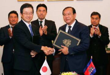 握手を交わす三上大使(左から2人目)とプラク・ソコン外相(同4人目)=3日、プノンペン(日本外務省提供)