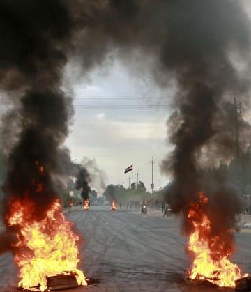 デモ参加者が火を付けて封鎖した道路=6日、バグダッド(AP=共同)