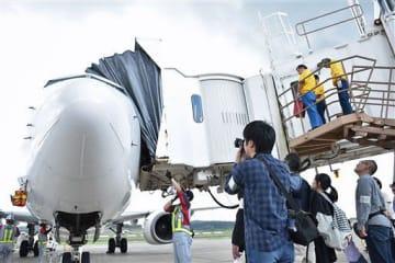 到着したばかりの飛行機を間近で見学する参加者ら