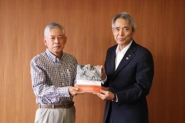 写真集「長崎の痕」を寄贈する長与九条の会の川野代表(左)と勝本教育長=長与町役場