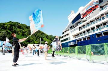 大漁旗を振ってクルーズ船を歓迎する市民ら