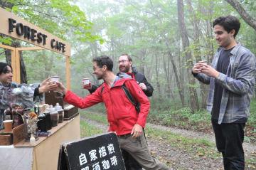 森の中に設置されたカフェを楽しむ参加者=6日午前11時45分、那須町湯本