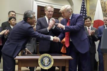 7日、米ホワイトハウスで行われた日米貿易協定の署名式に出席した(手前左から)杉山晋輔駐米大使、ライトハイザー通商代表、トランプ大統領(AP=共同)