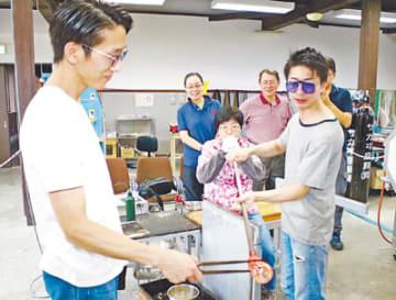 なないろKANの職員に教わりながら、吹きガラスを体験する参加者