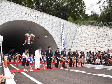 関係者や地元住民が集まり、テープカットとくす玉割りで祝った開通式=可児市大森、二野大森トンネル