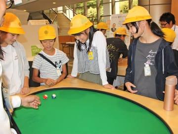 ビリヤード台で楕円の性質を学ぶ児童たち=本巣市上保、富有柿センター