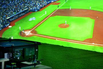 米大リーグ機構と提携したNTTが開催したイベントで、大型スクリーンに映し出されたレイズ―アストロズのア・リーグ地区シリーズの試合中継。手前は3台あるプロジェクターの一つ=7日、ニュージャージー(共同)