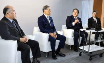 肩掛け式携帯電話を示し、創業時の電池開発への熱意を語る庄司社長(右から2人目)。左から高橋社長、台理事長。右は井出副知事