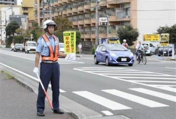 秋の全国交通安全運動期間中、日没前にドライバーに「ヘッドライトの早め点灯」を呼び掛ける警察官=9月27日夕、熊本市中央区