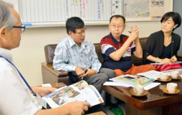 新玉小の徳本校長(左)にミャンマーでの世界寺子屋運動の成果を説明するミャットナインさん(右から2人目)ら