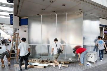 デモ隊に壊された中国系の銀行で修繕工事をする人たち=8日、香港(共同)